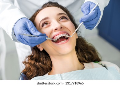 cropped view of dentist in latex gloves examining cheerful woman in braces with opened mouth