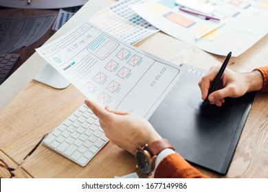 Cropped view of designer planning ux interface of website and using graphics tablet and laptop on table