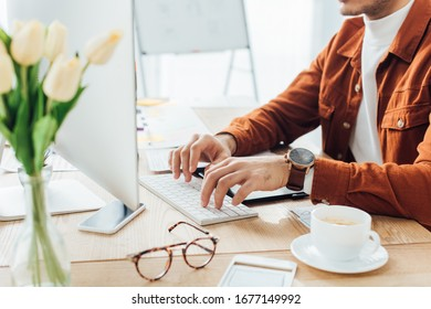 Cropped view of developer using computer near templates of ux design and coffee on table