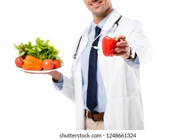 cropped view of doctor holding pepper and plate of fresh vegetables with greenery isolated on white, healthy eating concept