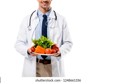 cropped view of doctor holding plate of fresh vegetables with greenery isolated on white, healthy eating concept