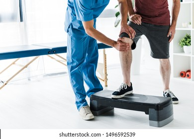 cropped view of doctor touching knee of mature patient on step platform