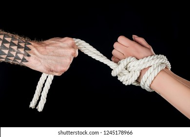 cropped view of dominant holding rope on submissive hands isolated on black