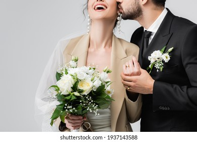 cropped view of elegant arabian groom kissing bride holding wedding bouquet and laughing isolated on grey