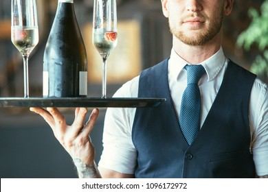 Cropped view of an elegant waiter is holding a tray with two glasses and a bottle of champagne in a restaurant
