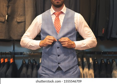 Cropped view of fashionable businessman in grey suit buttoning waistcoat