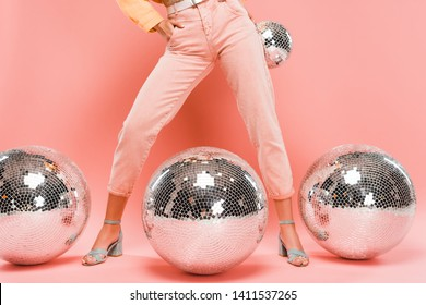 cropped view of fashionable girl posing with disco balls on pink
