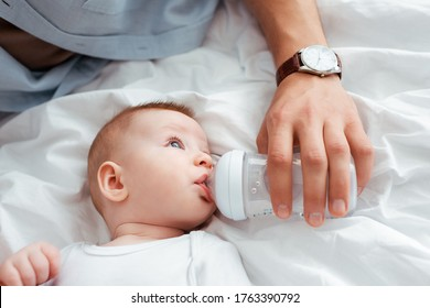 cropped view of father feeding cute little son from baby bottle with milk