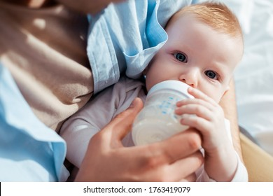 cropped view of father feeding son with milk from baby bottle