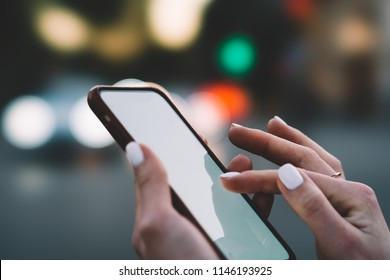 Cropped view of female fingers typing text message on blank display of modern smartphone on bokeh background.Woman's hands holding mobile phone and chatting online in social networks