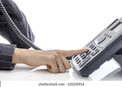 Cropped view of female hand dialing a phone number.