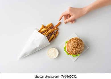 cropped view of female hand with french fries, homemade hamburger and mayonnaise, isolated on white