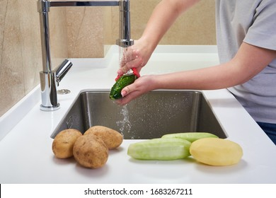 Cropped view of female hands peeling cucumber over Food waste disposer machine in sink in modern kitchen