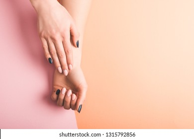 cropped view of female hands with pink and black nails on bicolor background, color of 2019 concept