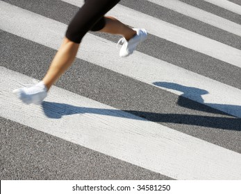 cropped view of female runner crossing street. Copy space