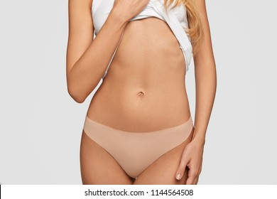 Cropped view of fit female shows her belly, has slim body, healthy pure skin, goes in for sport to stay fit, wears beige panties, isolated over white background. People, fitness and lifestyle concept