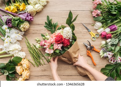 Cropped view of florist making flower bouquet on wooden surface