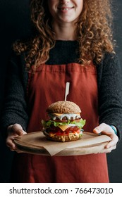 cropped view of girl in apron holding wooden board with big homemade cheeseburger