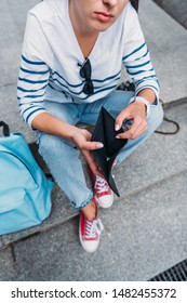 cropped view of girl holding empty black wallet while sitting on stairs