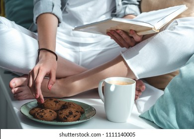 cropped view of girl reading book and eating cookies with coffee