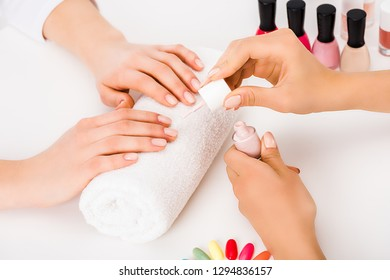 Cropped view of girl with short fingernails holding hands on towel while manicurist applying nail polish