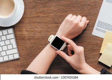 Cropped view of girl using smartwatch with blank screen on wooden background
