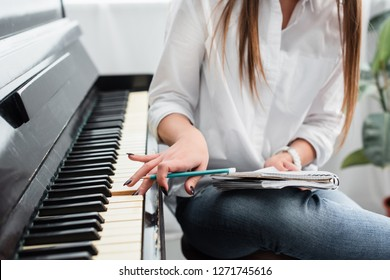 cropped view of girl in white shirt with notebook playing piano and composing music at home