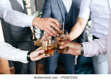 Cropped view of Group of friends guys with glasses of whiskey. Concept party, bachelor party