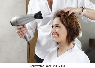 cropped view of hairstylist drying woman?s hair. Side view
