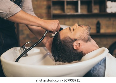 Cropped view hairstylist washing clients hair in barber shop