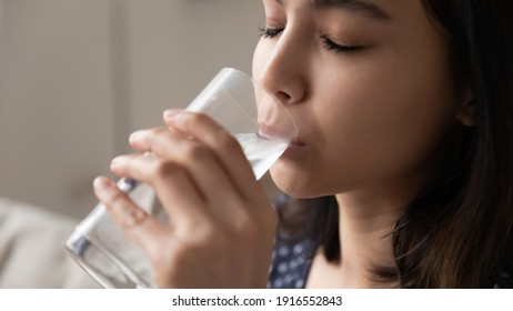 Cropped view of happy asian woman quenching thirst drinking cool clear potable water without gas. Close up of delighted young lady face enjoying taste of natural still aqua taking care of health skin