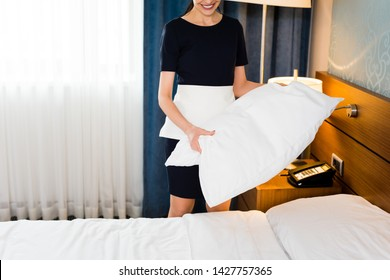 cropped view of happy housemaid holding white pillow in hotel room