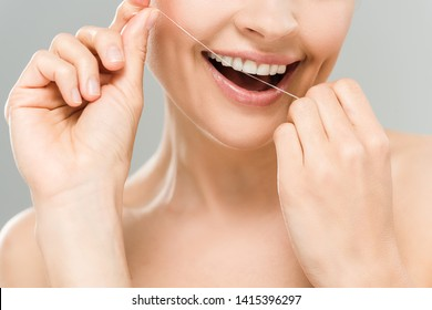 cropped view of happy naked woman flossing teeth with dental floss isolated on grey