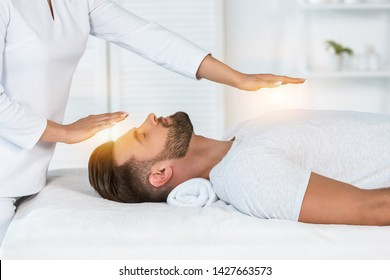 cropped view of healer putting hands above head while healing handsome man on massage table
