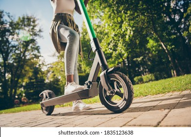 Cropped view of her she teenage teen trendy skinny slim fit hipster girl's legs riding kick scooter spending free time sunny day having fun, activity sport in forest wood outdoor youth hobby