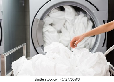 cropped view of housemaid near white bed sheets in laundry