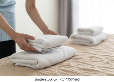 Cropped view of housemaid woman holding stack of white towels in hands, putting it on bed, standing inside bright and light bedroom