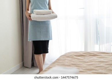 Cropped view of housemaid woman holding stack of white towels in hands, standing inside bright and light bedroom
