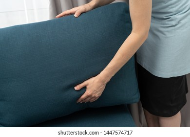 Cropped view of housemaid woman holding blue couch pillow in hands, standing inside bright and light bedroom