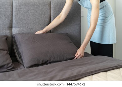 Cropped view of housemaid woman making bed, holding pillow in hands, standing inside bright and light bedroom