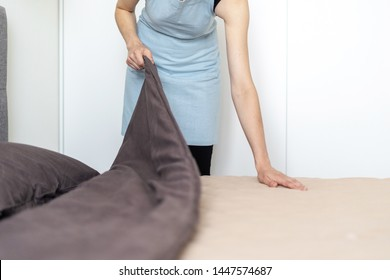 Cropped view of housemaid woman making bed, holding blanket in hands, standing inside bright and light bedroom