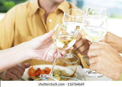 Cropped view image of four friends clinking their wine glasses and drinking a toast