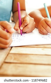 A cropped view image of the hands of a young mother and daughter doing homework working on multiplication tables together