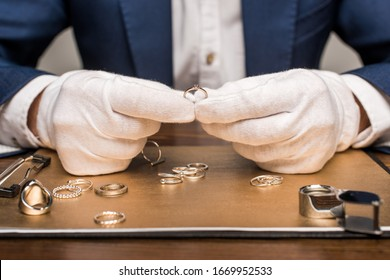 Cropped view of jewelry appraiser holding jewelry ring near board and magnifying glass on table isolated on grey