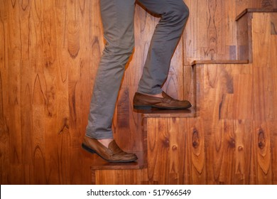 Cropped View of Legs of Man Climbing Wooden Stairs