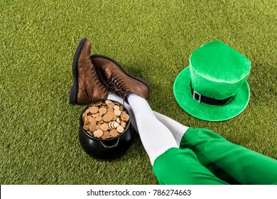 cropped view of leprechaun with pot of gold and hat sitting on green grass