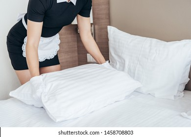 cropped view of maid in white apron and gloves holding pillow in hotel room