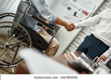 Cropped view of male office worker in a wheelchair shaking hand to his colleague while working together in the creative office. Teamwork. Disability and handicap concept. Business meeting