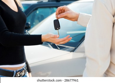 cropped view of man in car dealership giving car keys to client
