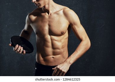 cropped view of a man with a dumbbell disc in his hand